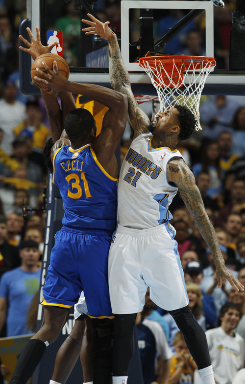 Golden State Warriors center Festus Ezeli (31), of Nigeria, is fouled while going up for a shot by Denver Nuggets forward Kenneth Faried, obscured, while forward Wilson Chandler (21) defends in the fourth quarter of Game 5 of their first-round NBA basketball playoff series, Tuesday, April 30, 2013, in Denver. The Nuggets won 107-100. (AP Photo/David Zalubowski)