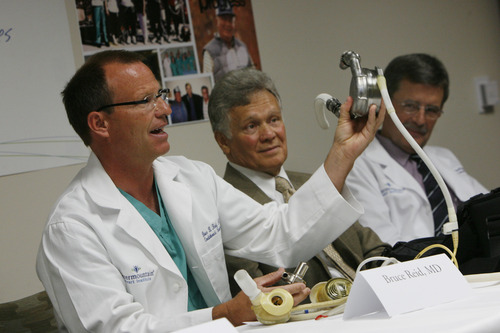Francisco Kjolseth  |  The Salt Lake Tribune Dr. Bruce Reid quotes Dr. Brad Rasmussen, far right as he compares early large heart devices, above, and the one in his right hand to the difference between 8 track and iPod technology. Pictured between them is Richard Mascarenas of Taylorsville who is currently fitted with an LVAD as he waits for a healthy heart for transplant. Patients, families and their medical team reunited to celebrate the 20th anniversary of the artificial heart program at Intermountain Medical Center on Tuesday, April 30, 2013.