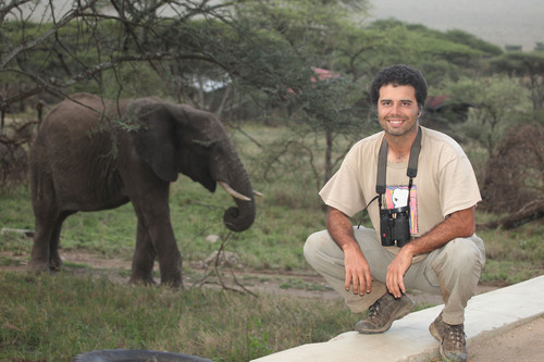 University of Utah assistant professor Cagan Sekercioglu at the Serengeti National Park in Tanzania in November 2009. The elephant in the background would later charge him. Sekercioglu escaped by running to higher ground. Courtesy Tanya Williams