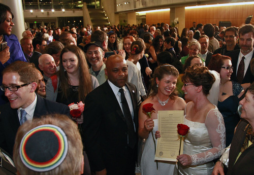 Just after midnight, Denver Mayor Michael Hancock, center left, stands after performing a civil union vows ceremony for Fran Simon, right, and her partner Anna Simon, at the Webb Municipal Building in Denver, Wednesday May 1, 2013. Fran and Anna Simon were the first to receive a civil union certificate.  In March 2013, the Colorado General Assembly passed SB-11, the Colorado Civil Union Act, which provides committed same-sex couples with legal protections and responsibilities. The act went into effect on May 1, 2013. (AP Photo/Brennan Linsley)