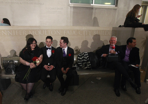 After midnight, Briceson Ducharme, second from left, sits with his partner Aaron Buck, center right, as they await their turn for a civil union vows ceremony, along with friend Errin Baumgartner, far left, who came in support, at the Webb Municipal Building in Denver, Wednesday May 1, 2013. In March 2013, the Colorado General Assembly passed SB-11, the Colorado Civil Union Act, which provides committed same-sex couples with legal protections and responsibilities. The act went into effect on May 1, 2013. (AP Photo/Brennan Linsley)
