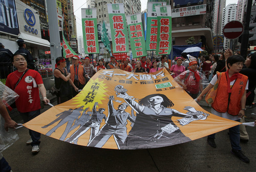 Workers and protesters hold a huge banner march to the government office during a May Day rally in Hong Kong, Wednesday, May 1, 2013. Hundreds of workers, local labor right groups and striking dockworkers join the annual rally to demand better wages and working conditions. (AP Photo/Vincent Yu)
