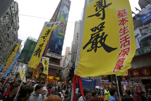 """Workers and protesters holding banners march to the government office during a May Day rally in Hong Kong Wednesday, May 1, 2013. Hundreds of workers, local labour right group and striking dockworkers join the annual rally to demand better wages and working conditions. Chinese in the banners read: """"Dignity."""" (AP Photo/Vincent Yu)"""