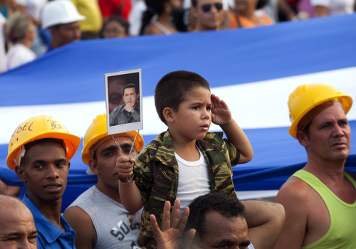 A youth wearing camouflage salutes as he hold an image of Venezuela's late President Hugo Chavez during a May Day march in Revolution Square in Havana, Cuba, Wednesday, May 1, 2013. (AP Photo/Ramon Espinosa)