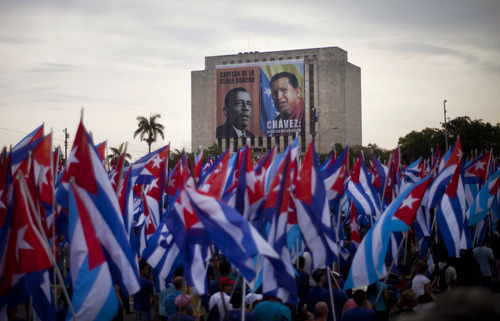 People carry Cuban flags during the annual May Day march near a building covered with an image of Venezuela's late President Hugo Chavez, right, and late Cuban union leader Lazaro Pena in Revolution Square in Havana, Cuba, Wednesday, May 1, 2013. Workers held protests, parades, strikes and other demonstrations in cities across the world on Wednesday. (AP Photo/Ramon Espinosa)