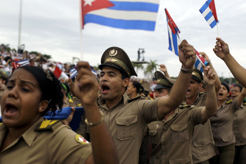 Soldiers shout revolutionary slogans and carry Cuban flags during the annual May Day march in Revolution Square in Havana, Cuba, Wednesday, May 1, 2013. Workers held protests, parades, strikes and other demonstrations in cities across the world on Wednesday. (AP Photo/Franklin Reyes)