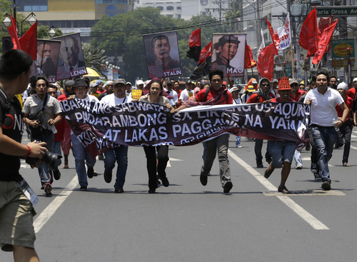 """Protesters, mostly workers, run to avoid blocking police officers as they try to get closer to the U.S. Embassy in Manila to mark International Labor Day Wednesday May 1, 2013 in Manila, Philippines. The workers, who have demanding wage increases for years, assailed President Aquino III for his Labor Day """"gift"""" of non-wage benefits.  The protesters have been clamoring for years for a P125-Peso ($3.125) across-the-board wage hike and condemn the Government's policy of outsourcing labor which allegedly eliminates job security. (AP Photo/Bullit Marquez)"""