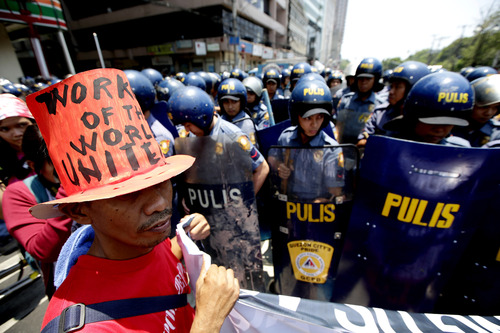 """Riot police block protesters as they try to march towards U.S. Embassy in Manila to mark International Labor Day Wednesday May 1, 2013 in Manila, Philippines. The workers, who have demanding wage increases for years, assailed President Aquino III for his Labor Day """"gift"""" of non-wage benefits.  The protesters have been clamoring for years for a P125-Peso ($3.125) across-the-board wage hike and condemn the Government's policy of outsourcing labor which allegedly eliminates job security. (AP Photo/Bullit Marquez)"""