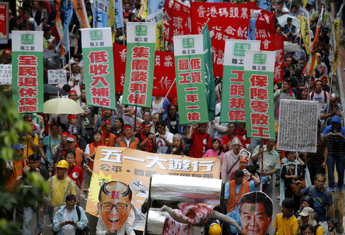 """Workers and protesters holding a defaced portrait of Hong Kong billionaire Li Ka-shing and banners reading """"right of collective negotiation,"""" """"low pay subsidy""""  and """"retire security"""" march to the government's office during a May Day rally  in Hong Kong Wednesday, May 1, 2013. Hundreds of workers, local labor rights groups and striking dockworkers joined the annual May Day rally in Hong Kong to fight for better wages and working conditions. (AP Photo/Vincent Yu)"""