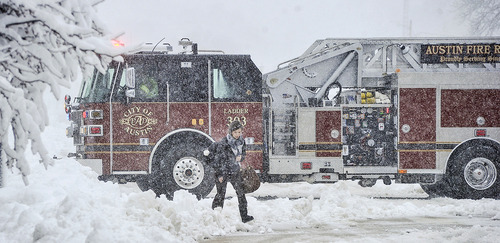 Kirsten Cole walks to work as an Austin fire truck returns to base from a call Thursday morning, May 2, 2013 in Austin, Minn. as heavy snow continues to fall on the area. Winter made a return appearance in southeastern Minnesota where residents are digging out of more than a foot of new snow.  (Associated Press/Austin Daily Herald, Eric Johnson)