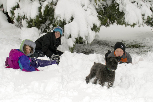 In this photo provided by Cory Howe Photography, Averie and Emma Howe, from left, and Sam Pfieffer, right, enjoy a school snow day as they pose Thursday, May 2, 2013 in Owatonna, Minn. A May snowstorm dumped heavy snow across parts of Minnesota and Wisconsin, resulting in dozens of school districts canceling classes. (AP Photo/Cory Howe Photography,HO)