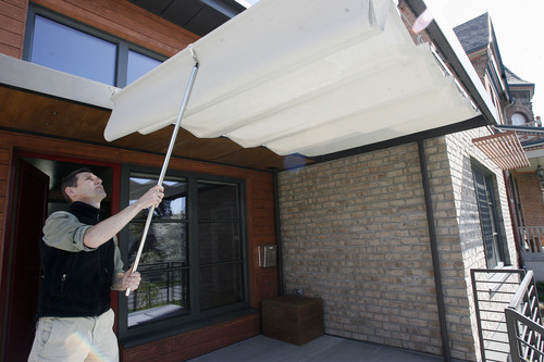 Rick Egan    The Salt Lake Tribune   Architect Dave Brach, shows the shade that can easily be put in place on the front porch of the energy efficient. home he designed, Friday, April 26, 2013. The Salt Lake City house is only the second in Utah to be given the certification that it is totally green and energy efficient.