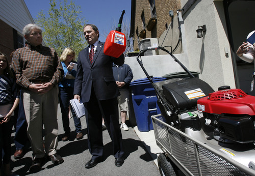Francisco Kjolseth  |  The Salt Lake Tribune Gov. Gary Herbert demonstrates some of the simple steps Utah citizens can take to help reduce emissions, including replacing fuel containers with ones that release fewer vapors, or using four-stroke lawnmowers at the home of Glen McBride across from the Capitol on Thursday. The Governor's Facebook will launch an info graphic promoting simple steps for cleaner air as he declares May 2013 Clean Air Month to encourage everyone's participation.