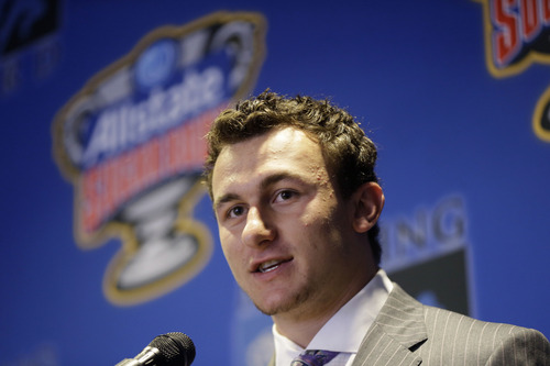 Heisman Trophy winner and Texas A&M quarterback Johnny Manziel, left, speaks as he receives the Manning Award, as the nation's top quarterback, during a luncheon, Thursday, May 2, 2013, in New Orleans. (AP Photo/Gerald Herbert)