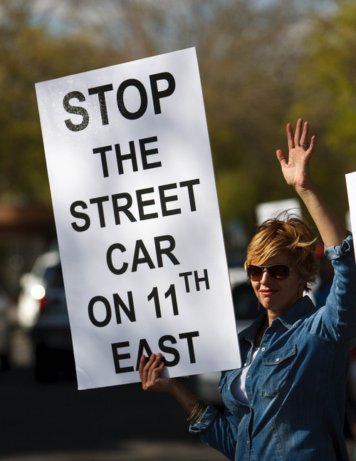 Trent Nelson  |  The Salt Lake Tribune Brenda Nibley, waving to passing cars, was among opponents to the 1100 East extension of the Sugar House Streetcar protesting Wednesday, May 1, 2013 in Salt Lake City.