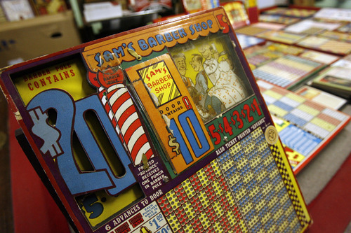 Francisco Kjolseth  |  The Salt Lake Tribune Clark Phelps a long-time Midvale businessman who owns what is probably the world's largest collection of punchboards displays the graphically interesting and colorful games of chance that were outlawed in 1979. With a small key you would push through the small hole that would punch out a piece of paper revealing your prize. Some have pennies, drawings, lighters, decks of cards, etc., as part of the display. People would buy a chance, punch out the ticket and hope to win at bars, coffee shops, even the Hotel Utah.