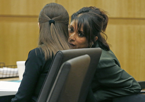 Mitigation specialist Maria DeLaRosa, right, whispers to defendant Jodi Arias as defense attorney Kirk Nurmi presents his closing arguments during her trial on Friday, May 3, 2013 at Maricopa County Superior Court in Phoenix.  Arias is charged with first-degree murder in the stabbing and shooting death of Travis Alexander, 30, in his suburban Phoenix home in June 2008. (AP Photo/The Arizona Republic, Rob Schumacher, Pool)