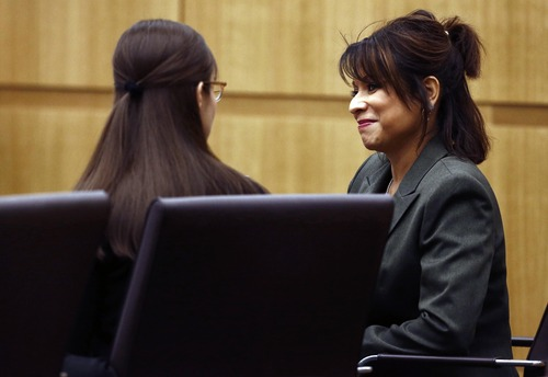 Mitigation specialist Maria DeLaRosa, right, talks to defendant Jodi Arias as defense attorney Kirk Nurmi presents his closing arguments  during her trial Friday, May 3, 2013 at Maricopa County Superior Court in Phoenix.  Arias is charged with first-degree murder in the stabbing and shooting death of Travis Alexander, 30, in his suburban Phoenix home in June 2008. (AP Photo/The Arizona Republic, Rob Schumacher, Pool)