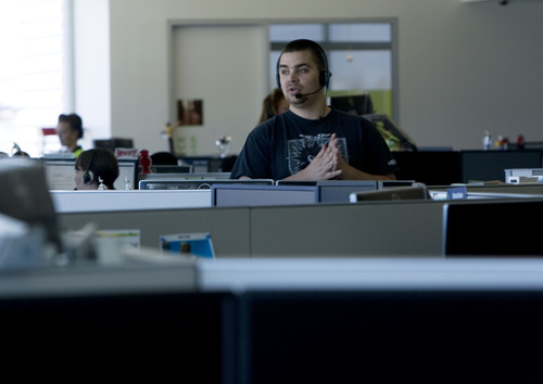 Kim Raff  |  The Salt Lake Tribune An eBay employee talks to a customer on the phone at his desk in the office space of eBay's new green certified building in Draper on May 2, 2013.
