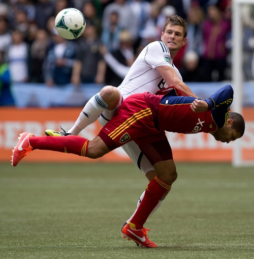 Vancouver Whitecaps' Brad Rusin, left, knocks down Real Salt Lake's Alvaro Saborio, of Costa Rica, as they vie for the ball during the first half of an MLS soccer game in Vancouver, British Columbia, on Saturday April 13, 2013. (AP Photo/The Canadian Press, Darryl Dyck)