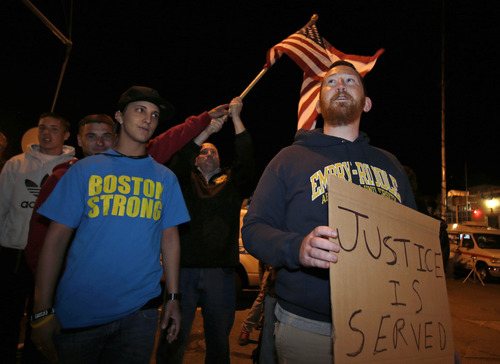"""Garrett Plath, right, holds a sign and Toni Zagami, left, wears a """"Boston Strong"""" shirt as they stand outside the Dyer-Lake Funeral Home in North Attleborough, Mass, where a vehicle believed to be carrying the body of Boston Marathon bombing suspect Tamerlan Tsarnaev arrived, Thursday, May 2, 2013. About fifteen people from the area stood outside the funeral home in protest. (AP Photo/Charles Krupa)"""