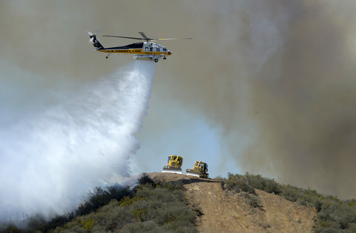 A helicopter makes a water drop on flames as bulldozers clear a firebreak along a hillside in Thousand Oaks, Calif., Thursday, May 2, 2013. A Ventura County Fire Department spokeswoman said the wildfire that broke out Thursday morning near Camarillo and Thousand Oaks, 50 miles west of Los Angeles, had spread to over 6,500 acres — more than 10 square miles - forcing evacuations of nearby neighborhoods. (AP Photo/Mark J. Terrill)