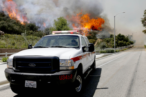 A Ventura County Firefighter  drives  near  a hotspot as smoke and fire billows over a hill near Thousand Oaks, Calif. on Thursday, May 2, 2013. Authorities have ordered evacuations of a neighborhood and a university about 50 miles west of Los Angeles where a wildfire is raging close to subdivisions.   (AP Photo/Nick Ut)