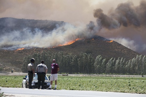 Police officers stand guard after after a blaze broke out during morning rush hour along U.S. 101 in the Camarillo area about 50 miles west of Los Angeles, Thursday, May 2, 2013, in Camarillo, Calif. (AP Photo/Ringo H.W. Chiu)
