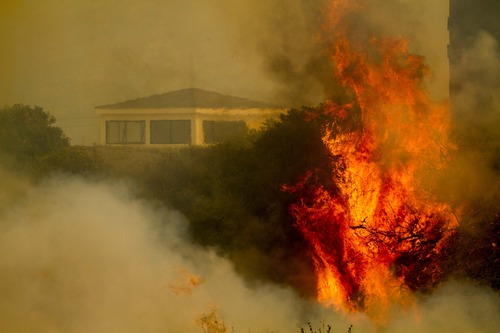 Flame and smoke rise from The Naval Base at Point Mugu, Calif., Friday, May 3, 2013. The 15 1/2-square-mile blaze was only 10 percent contained on Friday, and the work of more than 900 firefighters, aided by air tankers, was just beginning. (AP Photo/Ringo H.W. Chiu)
