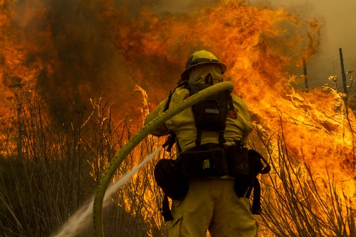 A firefighter battles the wildfire near the farmland along a hillside in Point Mugu , Calif. Friday, May 3, 2013.  A huge wildfire carved a path to the sea and burned on the beach Friday, but firefighters got a break as gusty winds turned into breezes. Temperatures remained high, but humidity levels were expected to soar as cool air moved in from the ocean and the Santa Ana winds retreated. (AP Photo/Ringo H.W. Chiu)