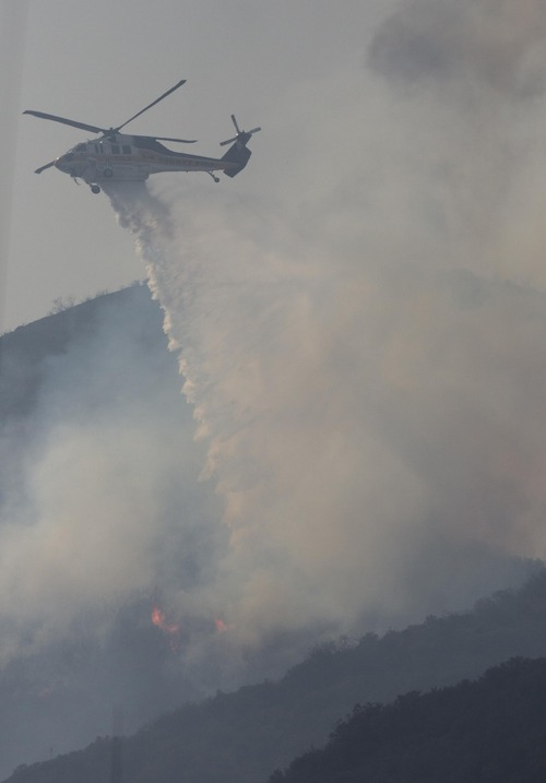A helicopter makes a water drop on flames as the wildfire burns along a hillside in Camarillo, Calif., Thursday, May 2, 2013. (AP Photo/Ringo H.W. Chiu)