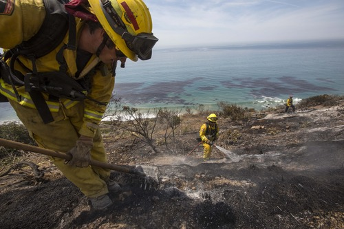 Firefighters work on the burned area along the Pacific Coast Highway, in Point Mugu, Calif., Friday, May 3, 2013.  A huge wildfire carved a path to the sea and burned on the beach Friday, but firefighters got a break as gusty winds turned into breezes. Temperatures remained high, but humidity levels were expected to soar as cool air moved in from the ocean and the Santa Ana winds retreated. (AP Photo/Ringo H.W. Chiu)