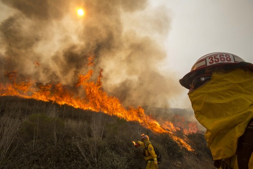 A firefighter watches a wildfire along a hillside in Point Mugu , Calif. Friday, May 3, 2013. Firefighters got a break as gusty winds turned into breezes, but temperatures remained high and humidity levels are expected to soar as cool air moved in from the ocean and the Santa Ana winds retreated. (AP Photo/Ringo H.W. Chiu)