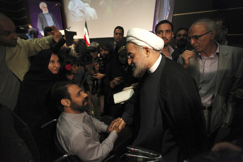 In this Thursday, May 2, 2013 photo, Iran's former nuclear negotiator, Hasan Rohani, a potential front-runner in the presidential race, center right, is greeted by a supporter, in a campaign rally in Tehran, Iran. For eight years, Iran's President Mahmoud Ahmadinejad has played the role of global provocateur-in-chief: questioning the Holocaust, saying Israel should be erased from the map and painting U.N resolutions as worthless. Now, a race is beginning to choose his successor -- candidate registration starts Tuesday for a June 14 vote -- and it looks like an anti-Ahmadinejad referendum is shaping up.  (AP Photo/Vahid Salemi)