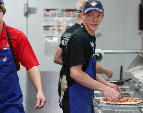 Trent Nelson  |  The Salt Lake Tribune Tuker Spanbauer works on pizzas under the eye of a camera at a Dominos Pizza location in Lehi Thursday, May 2, 2013. Dominos is streaming live video of the pizza-making process in the Lehi store.