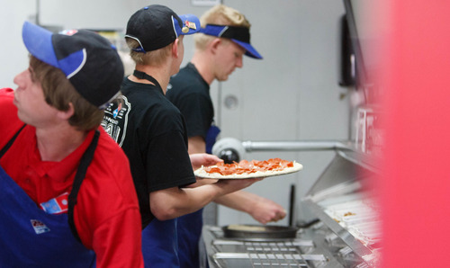 Trent Nelson  |  The Salt Lake Tribune Robbie Nelson, Tuker Spanbauer and Marc Aust work on pizzas under the eye of a camera at a Dominos Pizza location in Lehi Thursday, May 2, 2013. Dominos is streaming live video of the pizza-making process in the Lehi store.