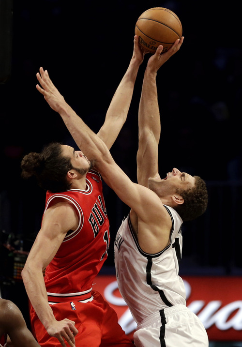 Chicago Bulls center Joakim Noah, left, blocks Brooklyn Nets center Brook Lopez during the second half in Game 7 of their first-round NBA basketball playoff series in New York, Saturday, May 4, 2013. (AP Photo/Julio Cortez)