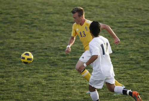 Chris Detrick  |  The Salt Lake Tribune Taylorsville's Randy Ivins (13) runs past Hunter's Steven Flores (17) during the game at Hunter High School Friday May 3, 2013.