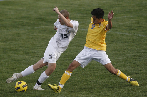 Chris Detrick  |  The Salt Lake Tribune Taylorsville's Edgar Estrade (9) and Hunter's Travis Brinkerhoff (15) go for the ball during the game at Hunter High School Friday May 3, 2013.