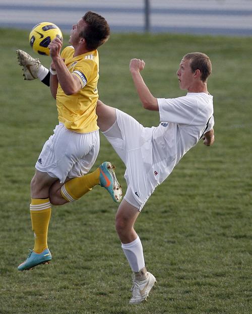 Chris Detrick  |  The Salt Lake Tribune Hunter's Travis Brinkerhoff (15) kicks the ball past Taylorsville's Randy Ivins (13) during the game at Hunter High School Friday May 3, 2013.