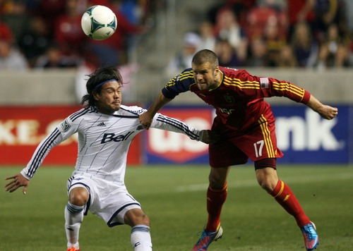Kim Raff  |  The Salt Lake Tribune (left) Vancouver Whitecaps FC midfielder Daigo Kobayashi (14) is held back by (right) Real Salt Lake defender Chris Wingert (17) as he heads the ball during a match at Rio Tinto Stadium in Sandy on May 4, 2013.  Real Salt Lake went on to win the game 2-0.