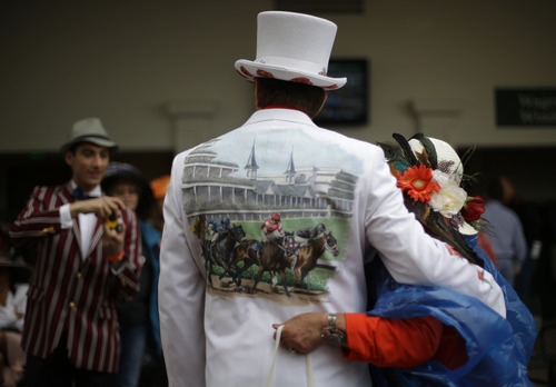 James Cowherd, center, from Las Vegas, Nev., poses for photos with other spectators before the running of the 139th Kentucky Derby at Churchill Downs Saturday, May 4, 2013, in Louisville, Ky. (AP Photo/David Goldman)