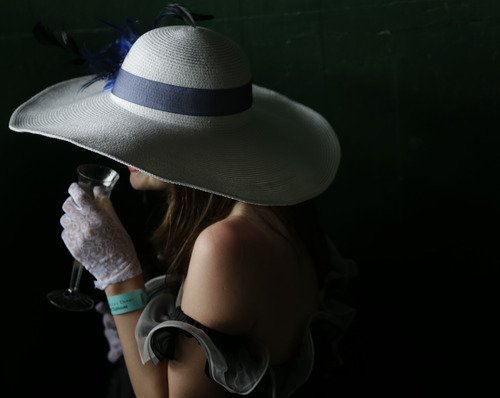 A spectator drinks chapagne with her fancy hat during the 139th Kentucky Derby at Churchill Downs Saturday, May 4, 2013, in Louisville, Ky. (AP Photo/Matt Slocum)