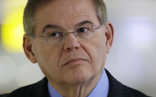 """FILE – In this March 1, 2013, file photo Sen. Robert Menendez, D-N.J., participates in a news conference at an airport in Newark, N.J. From the """"Keating Five"""" scandal, one of the more celebrated Congressional ethics cases, to more recent investigations, members of Congress have regularly run into trouble when they cross a sometimes blurry line between helping a supporter and engaging in a quid pro quo. As regards his own Senate Ethics Committee investigation Menendez has said, """"No one has bought me, No. 1. No one. Ever."""" (AP Photo/Mel Evans, File)"""