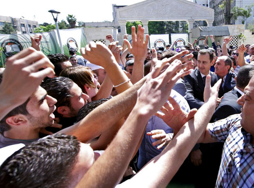 """This photo released on the official Facebook page of Syrian President Bashar Assad, shows Syrian president Bashar Assad, right, surrounded by bodyguards as young people, wave at him during the inauguration ceremony on Saturday of a statue dedicated to """"martyrs"""" from Syrian universities who died in the country's two-year-old uprising and civil war, in Damascus, Syria, Saturday, May. 4, 2013. Assad's second public appearance in a week came as Israeli officials confirmed the country's air force carried out a strike against Syria, saying it targeted a shipment of advanced missiles bound for the Lebanese militant group Hezbollah. (AP Photo)"""