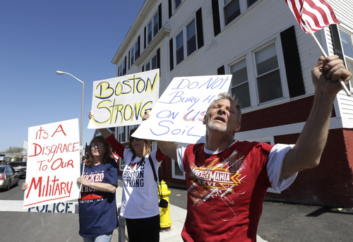 Herbert Robbins, of Worcester, Mass., right, joins with other demonstrators as they display placards and chant slogans on the street outside the Graham, Putnam, and Mahoney Funeral Parlors, in Worcester, May 5, 2013. Peter Stefan, owner and director of the funeral home, has pleaded for government officials to use their influence to convince a cemetery to bury Tsarnaev, but so far no state or federal authorities have stepped forward. (AP Photo/Steven Senne)