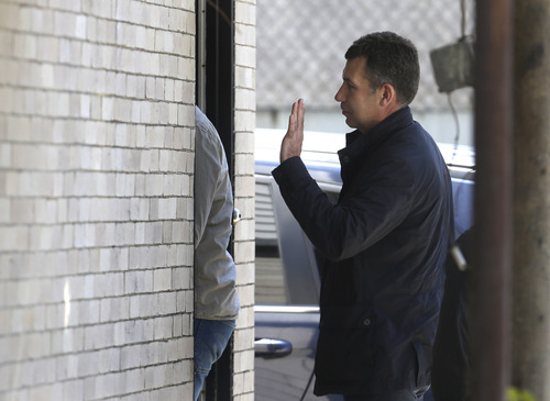 Ruslan Tsarni, uncle of killed Boston Marathon bombing suspect Tamerlan Tsarnaev, gestures as he enters the Graham, Putnam, and Mahoney Funeral Parlors, in Worcester, Mass., Sunday, May 5, 2013. Funeral director Peter Stefan has pleaded for government officials to use their influence to convince a cemetery to bury Tsarnaev, but so far no state or federal authorities have stepped forward. Men at left are unidentified. (AP Photo/Steven Senne)