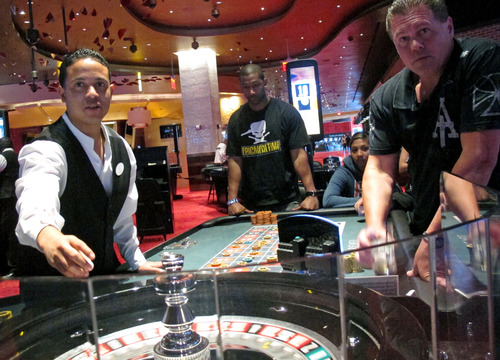 FILE - In this May 21, 2012 file photo, a dealer at Revel prepares for another round of roulette at the Atlantic City, N.J., casino as patrons await the result. Commercial casinos in the U.S. have made it almost all the way back from the hard times of the Great Recession. The American Gaming Association says revenue at non-Indian casinos hit $37.3 billion last year, just a shade under the all-time high reached in 2007. However, New Jersey experienced the largest decline in casino revenue, despite adding a 12th casino, Revel, which filed for Chapter 11 bankruptcy protection after less than a year of operation. Furthermore, Atlantic City's casinos were hurt by the after-effects of Superstorm Sandy, which kept many visitors away from months after the Oct. 29 storm. (AP Photo/Wayne Parry, File)