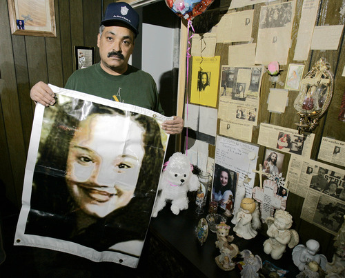 FILE - In this Friday, March 3, 2004 file photos shows Felix DeJesus, holding a banner showing his daughter's photograph, standing by a memorial in his living room in Cleveland. Cleveland police say two women who went missing as teenagers about a decade ago have been found alive in a residential area about two miles south of downtown. Cheering crowds gathered Monday night on the street near the home where police say Amanda Berry, Gina DeJesus and a third woman were found earlier in the day. The identity of the third woman hasn't been confirmed. (AP Photo/Tony Dejak, File)