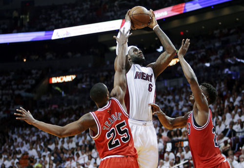 Miami Heat forward LeBron James (6) shoots against Chicago Bulls guard Marquis Teague (25) and forward Jimmy Butler, right, during the first half of Game 1 of the NBA basketball playoff series in the Eastern Conference semifinals, Monday, May 6, 2013 in Miami. (AP Photo/Lynne Sladky)